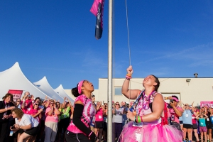 "TJ raises the flag ""We Will Never Give Up"" as the Michigan 3-Day walkers and crew cheer"