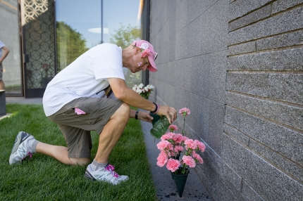 John places pink flowers in memory of his wife Martha on the Twin Cities 3-Day